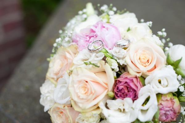 Zwei Fliegen mit einer Klatsche erwischt: die Ringe liegen mitten im Brautstrauß, fotografiert im goldenen Schnitt