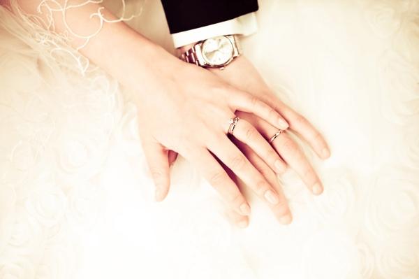 Die Eheringe sind ein Symbol für die Ewigkeit der Liebe und Verbundenheit. Das Hochzeitskleid bietet hier einen schönen Hintergrund.