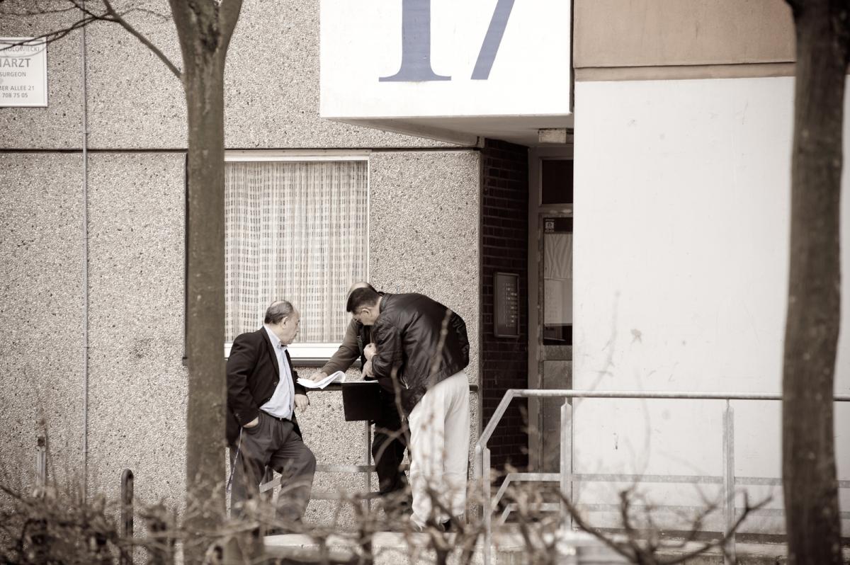 Eine Gruppe Ausländer vor der Arzt Praxis