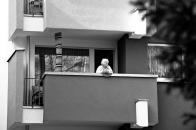 Eine alte Dame blickt vom Balkon