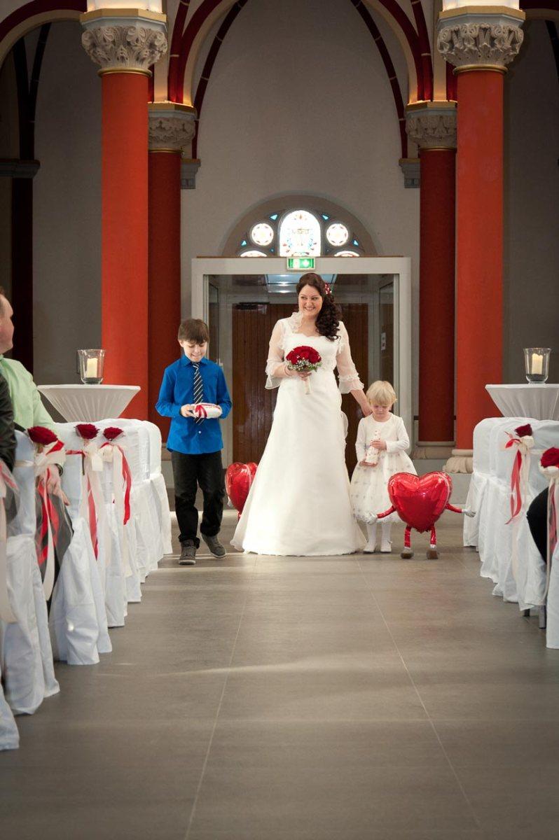 Die Braut wird von kleinen Gästen zum Altar geführt